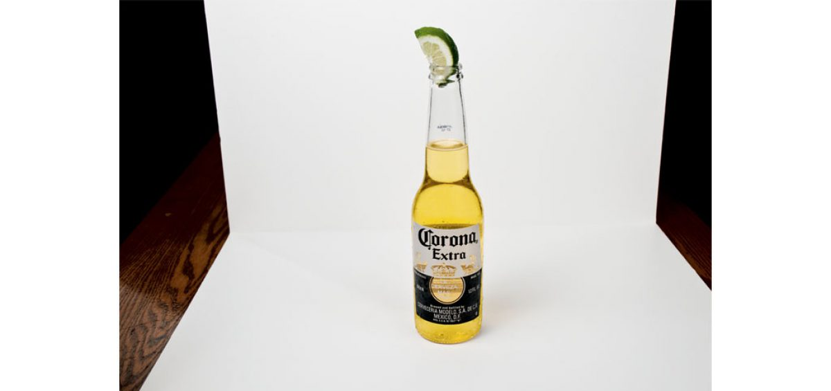 A picture of a Corona Beer, complete with lime, food photography by Roselle Food Photographer Controlled Color, Inc.