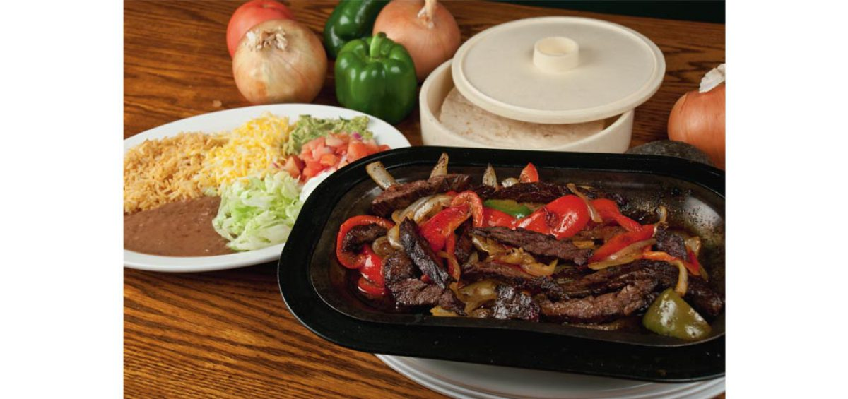 A picture of delicious, sizzling steak fajitas, food photography by Roselle Food Photographer Controlled Color, Inc.