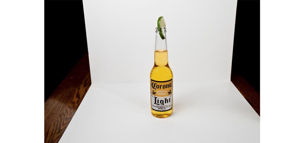 A picture of a Corona Light Beer, complete with lime, food photography by Roselle Food Photographer Controlled Color, Inc.